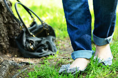 Woman legs in jeans and flats with bow in park Royalty Free Stock Image