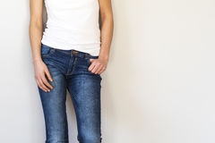 Woman legs in jeans on gray background royalty free stock image