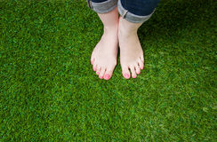 Woman legs in jeans standing  on grass Royalty Free Stock Images