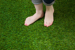Woman legs in jeans stepping on grass Royalty Free Stock Photography