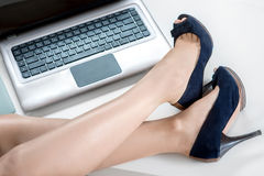 Woman legs and laptop. Woman legs with heels on the office table Stock Image