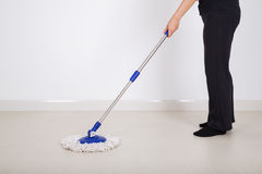 Woman legs with mop cleaning floor stock image