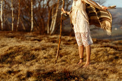 Woman legs in native indian american boho dress walking in windy. Sunny evening mountains, holding feathers stock photos