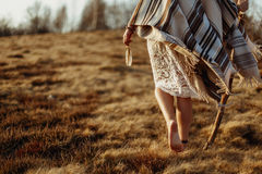Woman legs in native indian american boho dress walking in windy. Sunny evening mountains, holding feathers royalty free stock photography