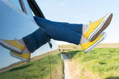 Woman legs out of the car window Stock Photography