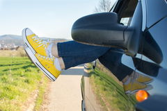 Woman legs out of the car window Royalty Free Stock Photos
