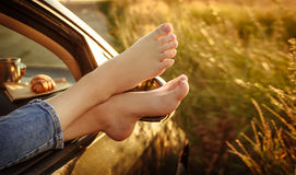 Woman legs out the windows in car . royalty free stock images