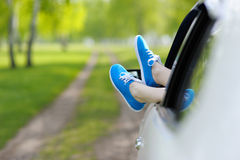 Woman legs out the Windows in the car among the trees. Royalty Free Stock Image