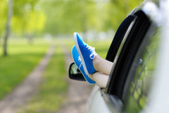 Woman legs out the Windows in the car among the trees. Royalty Free Stock Photo