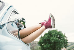Woman legs outside a vintage car Stock Photos