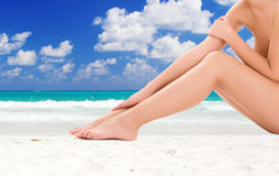 Woman legs over tropical beach background Stock Images