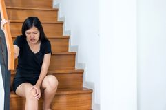 Woman legs pain with touching her knee and walking up stairs at home royalty free stock images