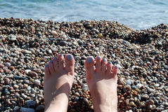 Woman legs on pebble beach. First person perspective of woman legs lying on pebble beach stock photo