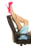 Woman legs in pink heels lay on office chair back Stock Photo