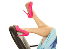 Woman legs in pink heels lay on office chair one kicked up. A woman with her feet kicked up on her business chair Royalty Free Stock Images