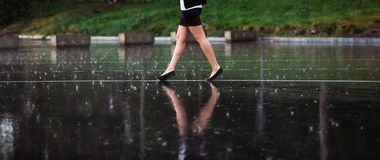 Woman legs and rain drops on asphalt.  Royalty Free Stock Photography