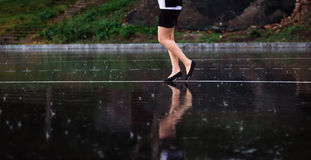 Woman legs and rain drops on asphalt.  Royalty Free Stock Image