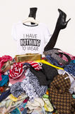 Woman legs reaching out from a big pile of clothes with a t-shirt saying nothing to wear. Stock Photo