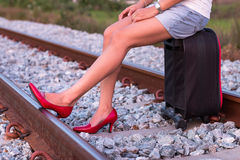 Woman legs in red high heel shoes and sitting on suitcase in rai. Lway Stock Photos