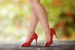 Woman legs in red high heels walking. On urban street Stock Photos