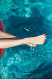 Woman legs with red nail in swimming pool Royalty Free Stock Photos