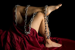 Woman legs and red sheet on black chain wrapped Stock Image