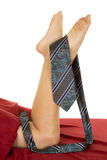 Woman legs with red sheet knees down tie on feet Royalty Free Stock Photography