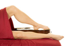 Woman legs with red sheet one foot on guitar Stock Images