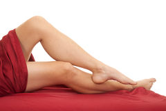 Woman legs red sheet one foot over other leg Royalty Free Stock Photos