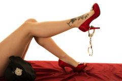 Woman legs in red shoes with handcuffs and a tattoo Stock Photography