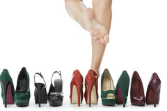 Woman Legs in Red Shoes Between Other High Heels stock image