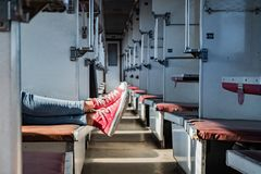 Woman legs in red tennis shoes in a vintage empty train car. Fem. Ale in canvas shoes rests on seats of an old soviet economy class carriage royalty free stock photos