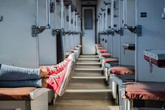 Woman legs in red tennis shoes in a vintage empty train car. Fem. Ale in canvas shoes rests on seats of an old soviet economy class carriage stock image