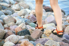 Woman legs on the rocks Stock Images