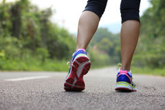 Woman legs running at forest trail Stock Photo