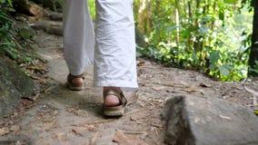 Woman legs in sandals walk along narrow path in rainforest
