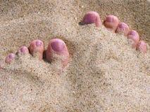 Woman legs on sandy beach. First person perspective of woman legs lying on sandy beach royalty free stock photos