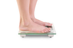 Woman legs on scales. Closeup shoot of young caucasian woman legs on scales. Isolated over white background Royalty Free Stock Photography