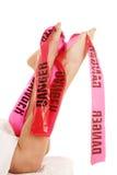 Woman legs sheet danger tape Royalty Free Stock Photo