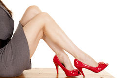 Woman legs sit gray dress red heels Royalty Free Stock Photo