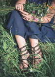 Woman legs sitting in grass on summer meadow Royalty Free Stock Photography