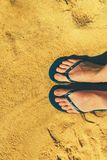 Woman legs in slippers on yellow sand background. Blue flip flops on beach. Copy space, top view. Holiday and travel. Concept Royalty Free Stock Photo