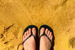 Woman legs in slippers on yellow sand background. Blue flip flops on beach. Copy space, top view. Holiday and travel. Concept Stock Photos