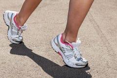 Woman legs in sneakers on asphalt Stock Images