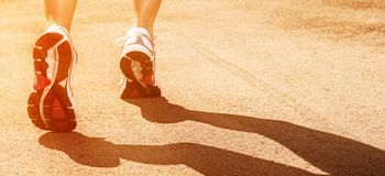 Woman legs in sneakers on asphalt Royalty Free Stock Photography