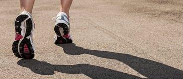 Woman legs in sneakers on asphalt Stock Image