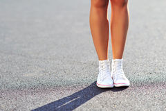 Woman legs in sneakers. Outdoor Stock Photography