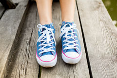 Woman legs in sneakers on a wood Royalty Free Stock Photo