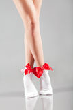 Woman legs with socks and red ribbons. Woman legs with white socks and red ribbons royalty free stock photos