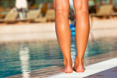 Woman legs standing on the edge of swimming pool Stock Photos